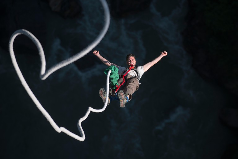 A man smiles for the camera while bouncing back on a bungee jump.