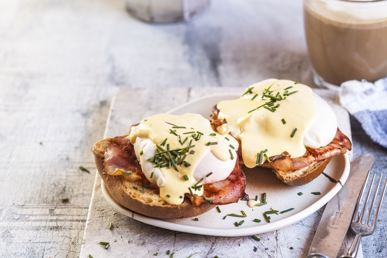 egg benedict with slices of bacon on toast, poached egg and hollandaise