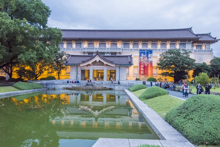People walking next to the entrance of the Honkan museum building that holds the Japanese Gallery in the Tokyo National Museum in the Ueno Park at the Taito ward in Tokyo city, Japan.