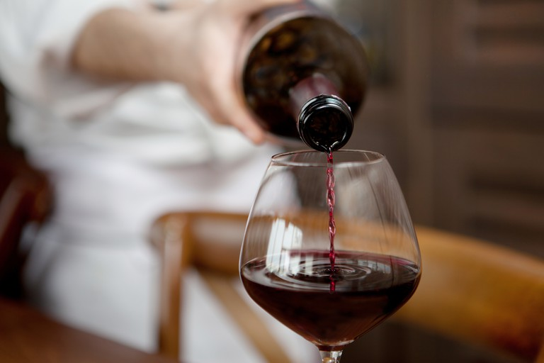 Waiter pours red wine
