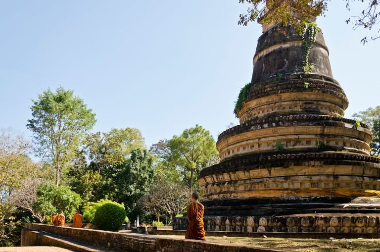 Buddhist monks in orange robes walk by stupa at Wat U Mong temple