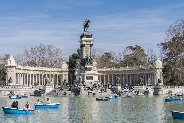 People rowing in the pond next to the Monument to Alfonso XII of Spain, in the Retiro Park (Parque del Retiro) at Madrid city, Spain.