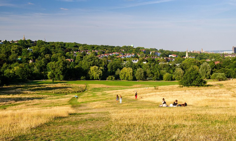 London, England, UK - August 20, 2013: People walk in the sunshine on Parliament Hill, part of Hampstead Heath park in north London, with the neighbou