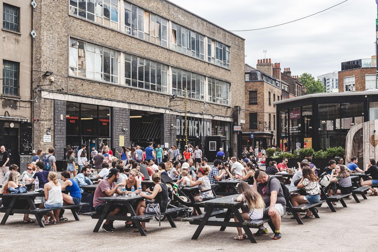 People eating and socialising in the Old Truman Brewery's Ely's Yard at Sunday UpMarket, one of 5 markets of The Truman Markets