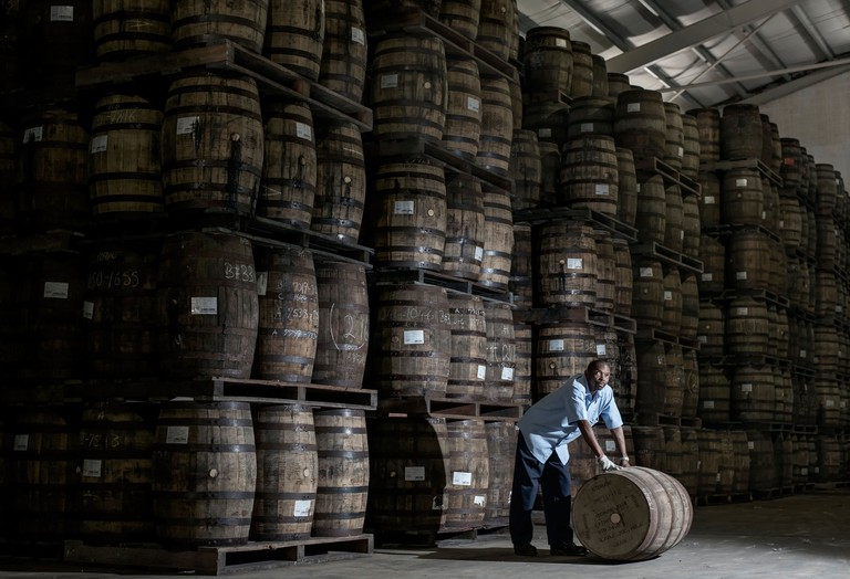 A distillery worker moving wooden barrels at the Mount Gay rum distillery in St Lucy Parish, Barbados, Caribbean