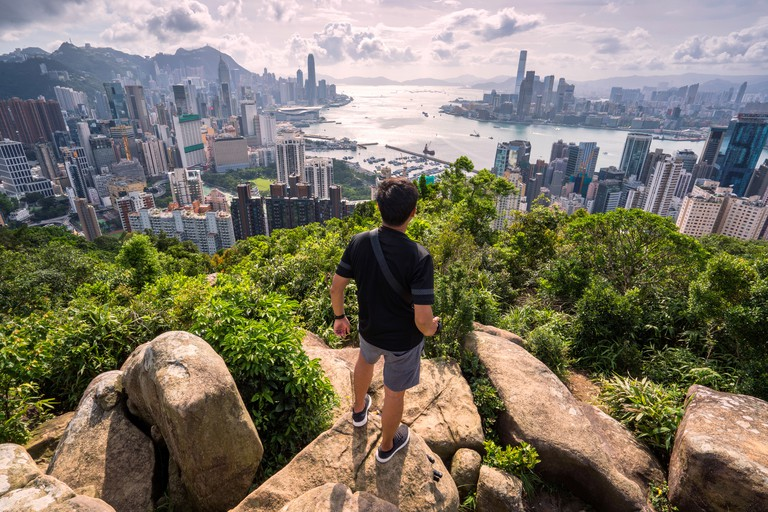 Asian man traveler is visiting at Braemar hill peak,tourist looking to Hong Kong City view and Victoria harbor