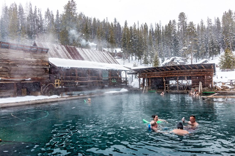 People soak in the 100 degree water of the main pool at Burgdorf Hot Springs near McCall, ID, during a light snowfall. The springs can be reached in w