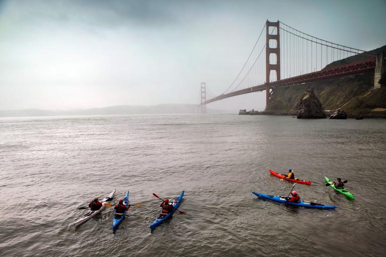 USA, California, San Francisco, individuals endure the cold to kayak under the Golden Gate Bridge