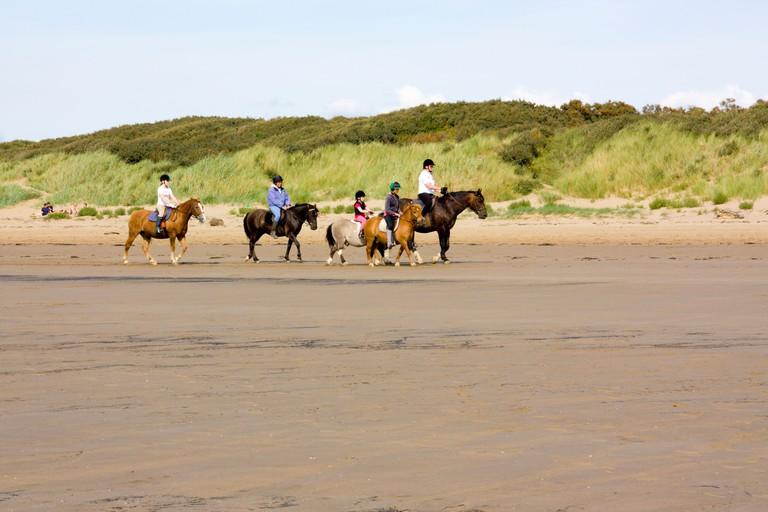 Group of people riding horses on Berrow Beach Somerset England UK