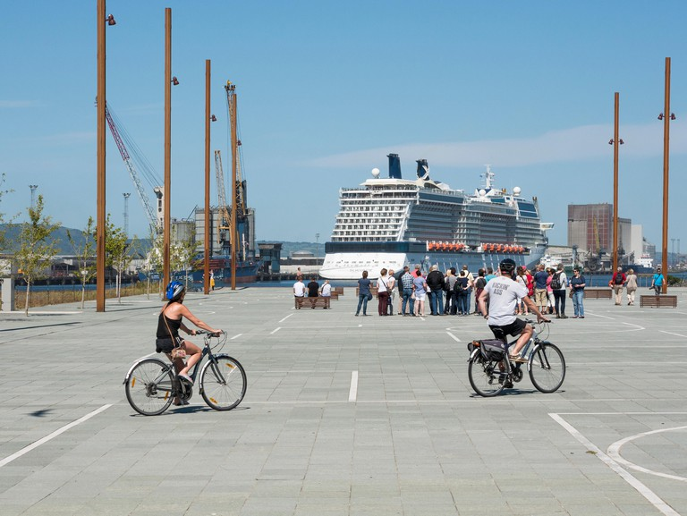 Belfast, Northern Ireland, UK. 24 July 2017. UK weather: Visitors on a walking tour on the Slipway in Titanic Quarter enjoy sunshine and a temperature of 24C.  The cruise liner Celebrity Silhouette can be seen in the background. Credit J Orr/Alamy Live Ne