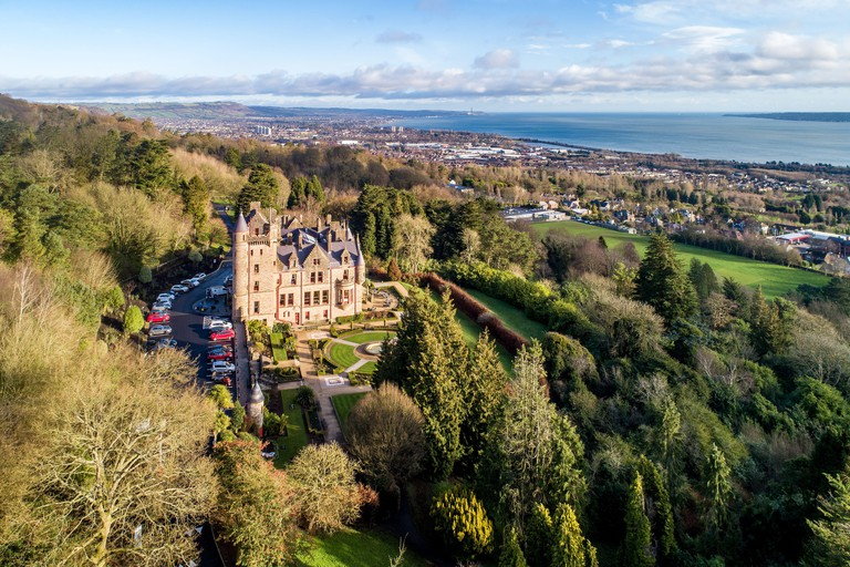 Belfast castle. Tourist attraction on the slopes of Cave Hill Country Park in Belfast, Northern Ireland. Aerial view. Belfast Lough and city in the ba