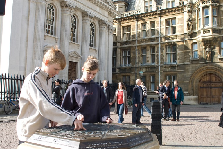 Boy and girl in Cambridge looking at an engraved map in city centre