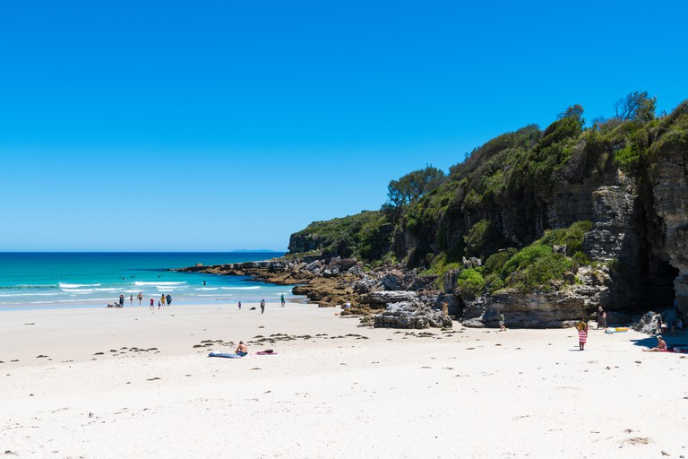 Cave Beach, NSW, Australia-December 24, 2018: People enjoying the sunny weather at Cave beach in Jervis Bay, a quiet getaway location to enjoy surf an
