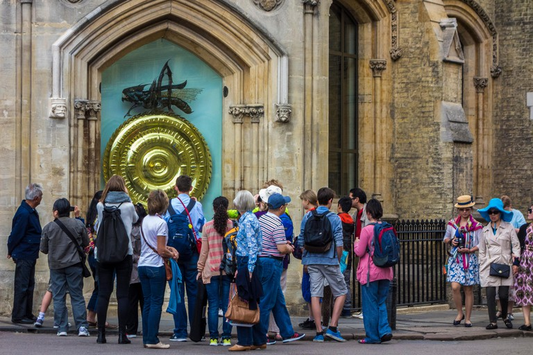 Tourists gather by the unusual and unique Corpus Clock in Cambridge