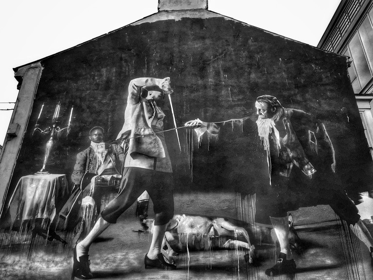 A monochrome mural on the gable wall of The Black Box Performance & Arts Venue in Hill Street, Cathedral Quarter, Belfast, Northern Ireland. The picture depicting two men duelling. © COLIN HOSKINS.