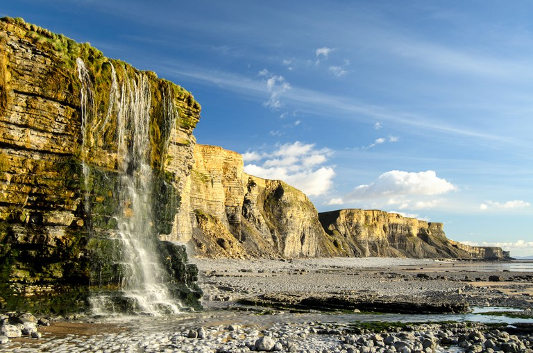Waterfall over cliffs at Dunraven Bay, Southerndown, South Wales, UK
