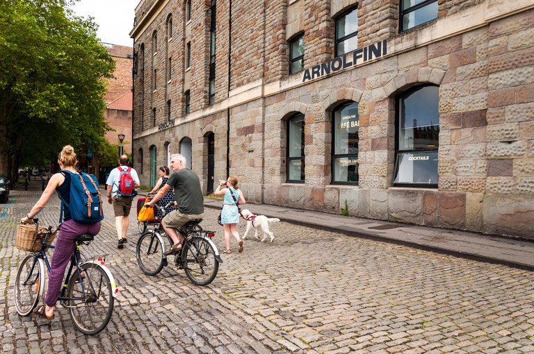 People cycle and walk past Arnolfini Arts centre, Bristol, England, UK