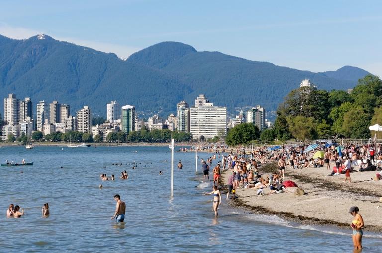 People sunbathing and swimming in English Bay at Kitsilano Beach, Vancouver, British Columbia, Canada