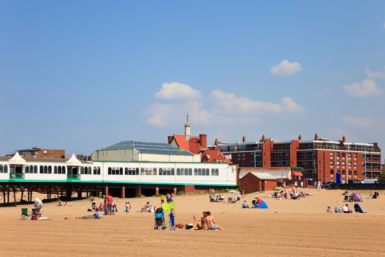 Lytham St Annes, Lancashire, England, UK. Holidaymakers on sandy beach by the pier in seaside resort