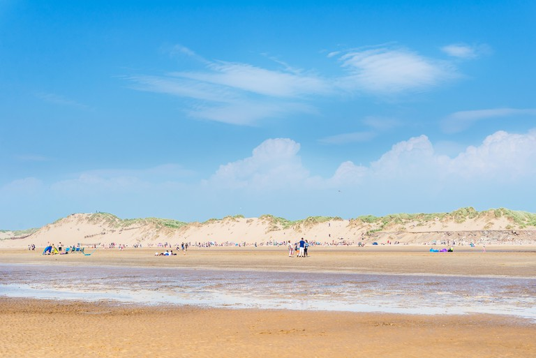 Liverpool, Great Britaon - 10 June, 2018: Sandy Formby Beach  near Liverpool on a sunny day with lots of people. Unusual hot summer in Great Britain.