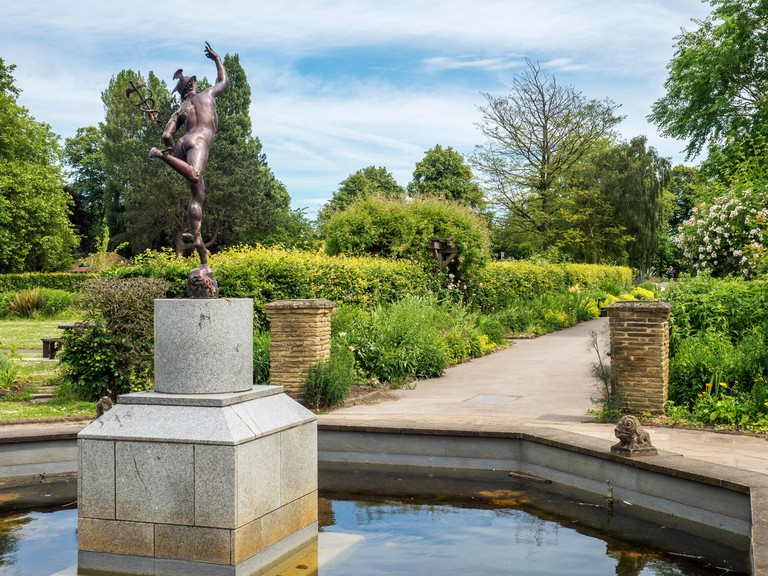 Pond with statue and herbaceous borders at Rowntree Park in York Yorkshire England