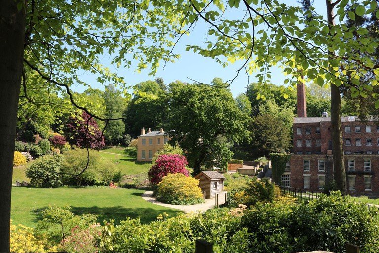 View of  National Trust Quarry Bank House and mill and gardens in the spring framed by trees