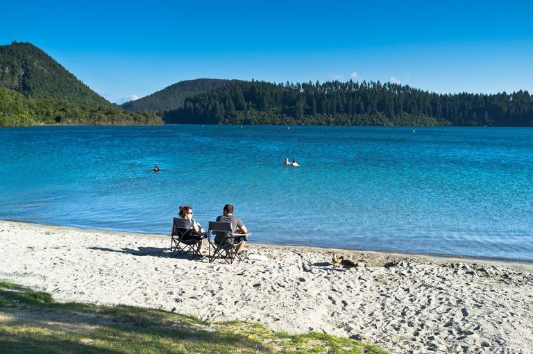 dh Blue Lake ROTOROA NEW ZEALAND Couple sitting on sand shore beach Lake Tikitapu. Image shot 2013. Exact date unknown.