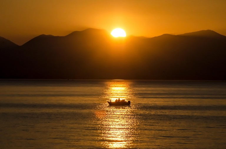 Sunset, lake sparkling.Fishermen driving a small fishing boat in fishing.