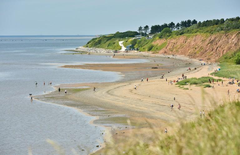 People enjoying the good weather on the beach at Thurstaston, Wirral, England, UK.
