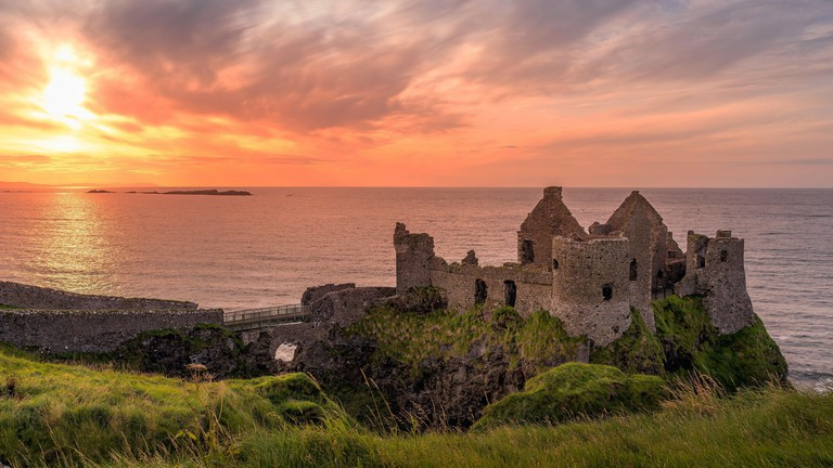 Dunluce Castle on the cliff in Bushmills, Northern Ireland at sunset.