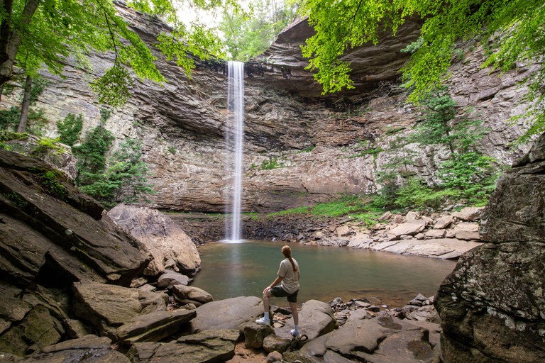 Woman standing and admiring the majestic Ozone Falls in Crossville, Tennessee which plunges 110 feet over a sandstone rock into a deep pool.
