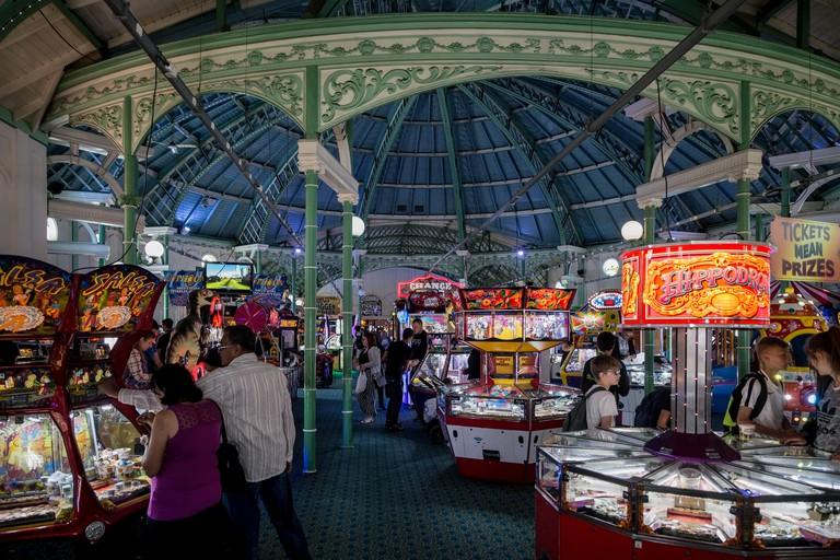 Visitors enjoying amusement arcade on Brighton Palace Pier, Brighton, East Sussex, England, UK