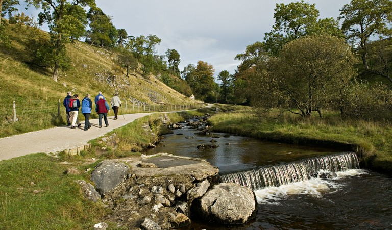 Group of adults walking alongside the beck on a nature walk towards Ingleborough Cave Yorkshire dales England UK