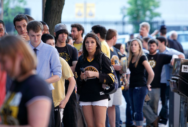 Boston Bruins hockey fans line up to enter a bar in Boston for game seven of the Stanley Cup being played in Vancouver