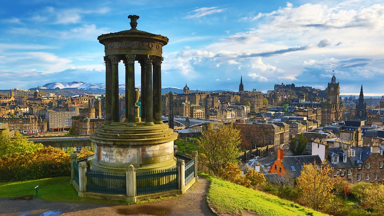 General city skyline view from Calton Hill showing the Dugald Stewart Monument and Edinburgh Castle in Edinburgh, Scotland, UK