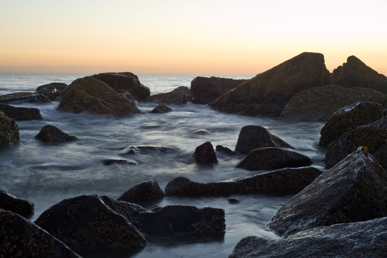 The sun sets over a rocky portion of Coronado Beach on Coronado Island
