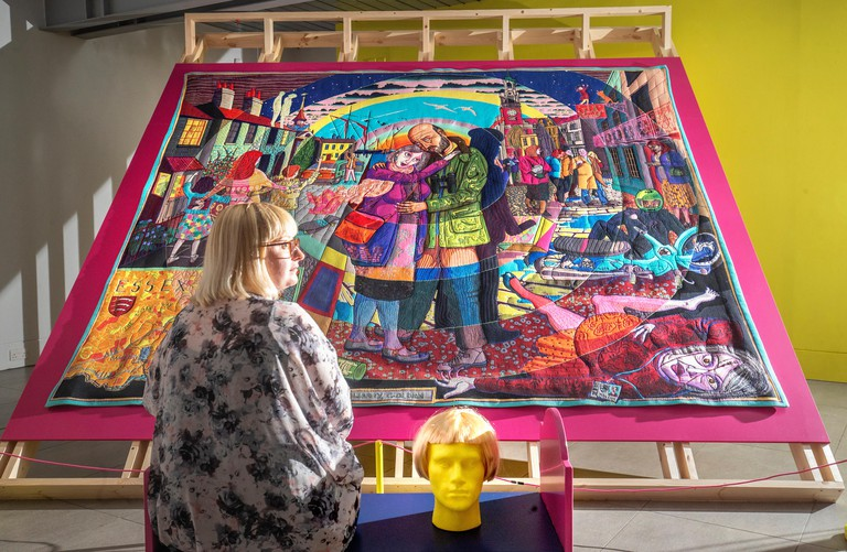 Gallery front of house manager Sinead Bracken takes a look at some of the tapestry work by artist Grayson Perry before the exhibition is opened to the public at the Dovecot Studios in Edinburgh.