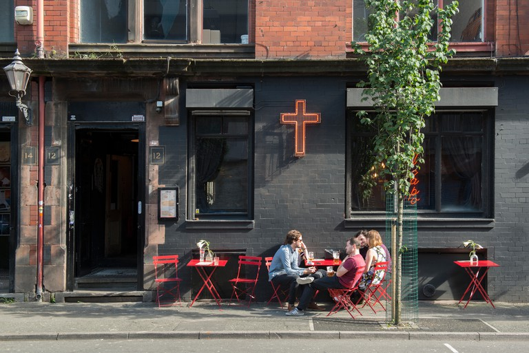 People enjoying a drink outside El Capo bar located on Tariff Street in the Northern Quarter area of Manchester.