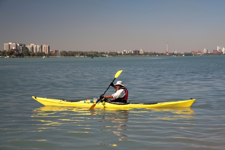 Detroit, Michigan - A man paddles a wooden kayak in the Detroit River.