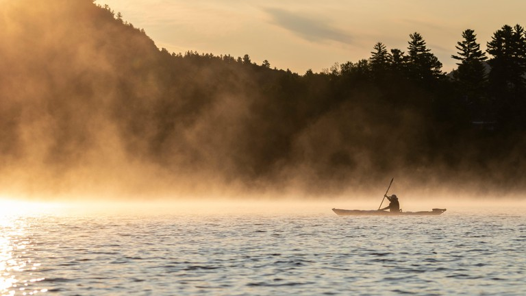 Kayaker paddling on  Lac du Poisson-Blanc at sunrise, Quebec.