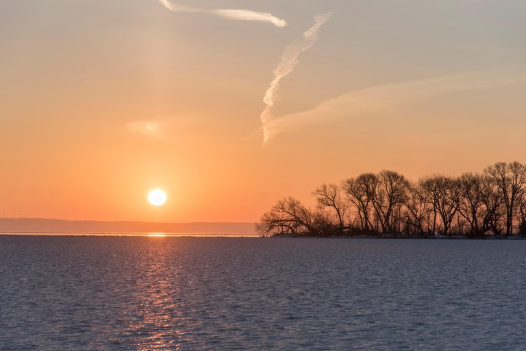 Ice cold sunrise over a partially frozen Lake Winnebago.  The highly reflective part on the horizon must either be open water ne