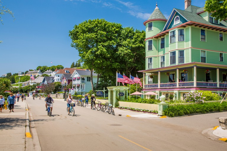 Tourists riding bikes on resort island of Mackinac Island Michigan