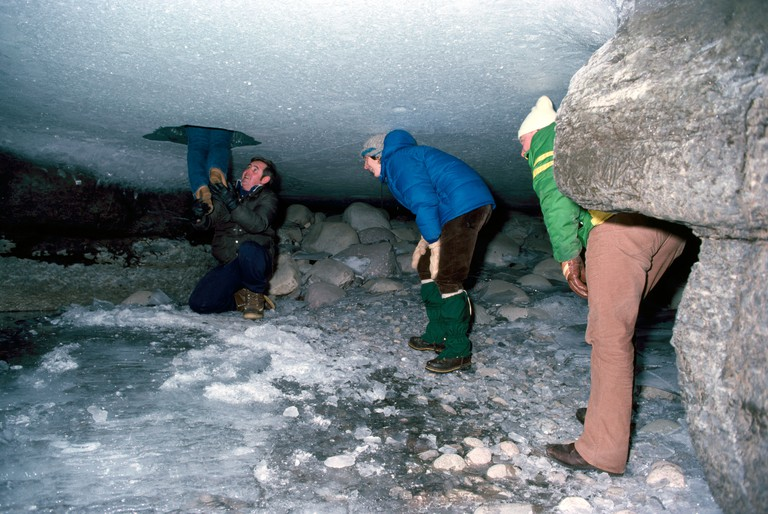 Tourists on an Ice Walk exploring under the Ice at the River Bottom of Maligne Canyon in Jasper National Park Alberta Canada