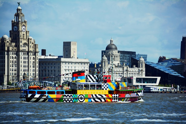 "The Mersey Ferry ?Dazzle ship? Snowdrop sailing past Liverpool's ""Three Graces"" on the river Mersey."