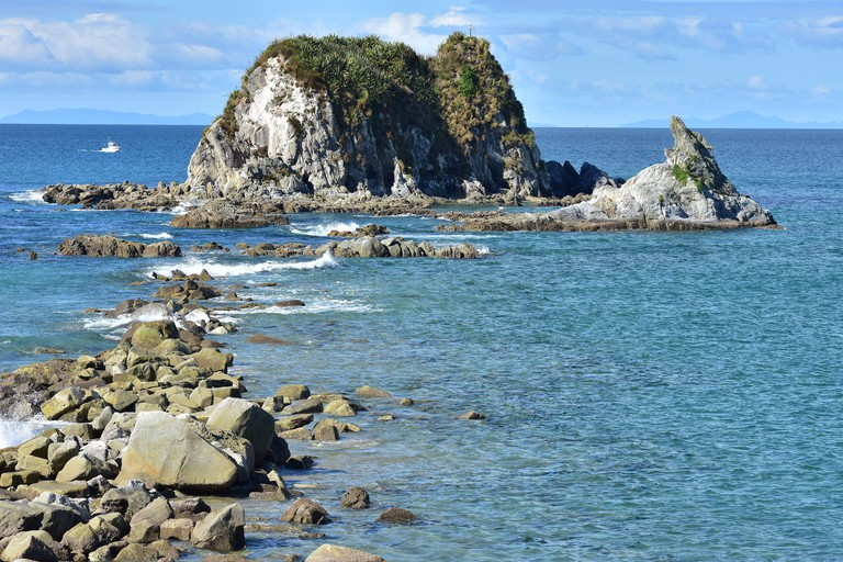 Horizontal view of rocks stretching from shore to rocky islet near harbor mouth in Mangawhai Heads.