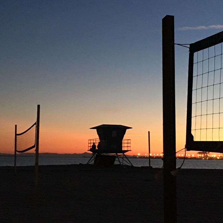 Volleyball nets and lifeguard tower at sunset on Junipero Beach in Long Beach, CA, USA