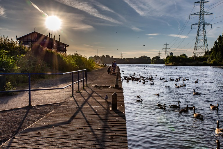 Sale Water Park and Water Sports Centre and lake with a family feeding ducks / water fowl on the lake and the son low in the evening sky