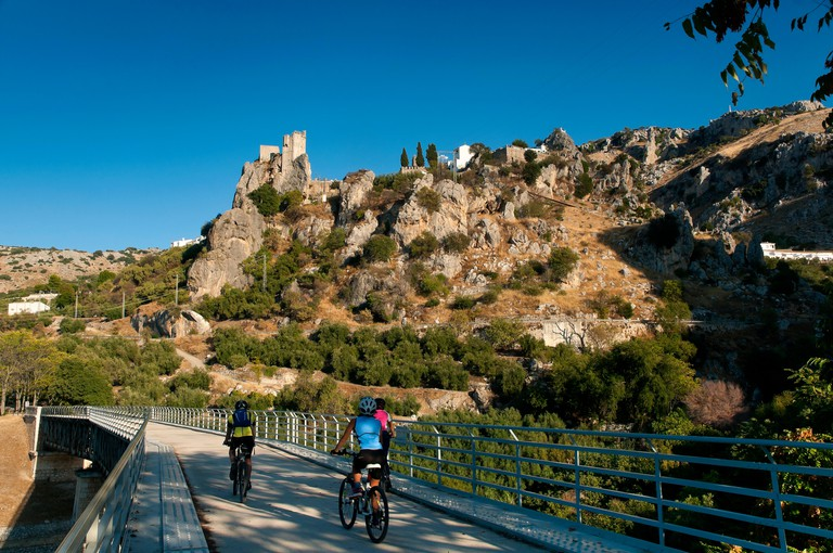 "Greenway of the Subbetica (old railway line of the so-called ""oil train"") - viaduct, cyclists and rocky castle (9th century). Zuheros. Cordoba provinc"