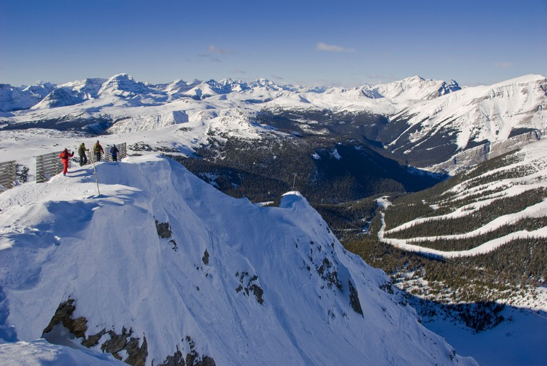 Skiers walk along the edge of Delirium Dive, Sunshine Village Ski Resort, Banff National Park, Alberta, Canada.