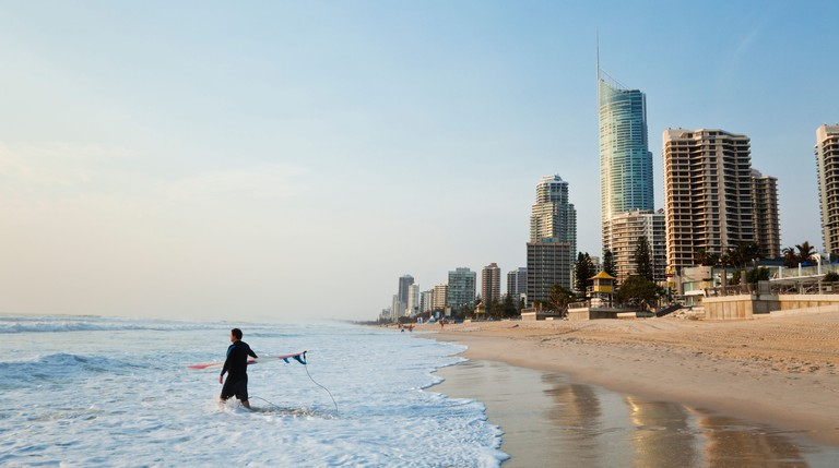 Surfer walking into surf with city skyline in background. Surfers Paradise, Gold Coast, Queensland, Australia